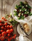 Salad with feta cheese and fresh tomatoes in basket, top view — Stock Photo