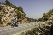 Жінка їзда мопед вздовж гірській дорозі Самос, Греція — стокове фото