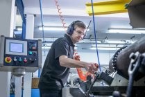 Engineer in ear defenders and safety glasses cleaning steel bar on lathe — Stock Photo