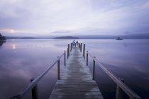 Пара на пристані на спокійному озера Камбрія, Англія, Великобританія — стокове фото