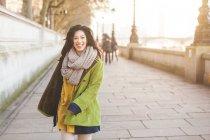 Вид спереди молодой женщины, прогулки вдоль берега реки Темзы, глядя на камеру, улыбаясь, Лондон, Великобритания — стоковое фото