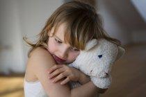 Menina angustiada segurando no ursinho de pelúcia — Fotografia de Stock