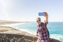 Jovem mulher tomando selfie smartphone na costa, El Cotillo, Fuerteventura, Espanha — Fotografia de Stock