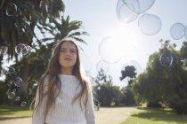 Mädchen im Park, umgeben von Blasen, die wegschauen — Stockfoto