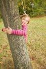 Smiling girl hugging tree outdoors — Stock Photo