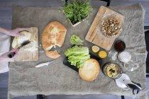 Recortar imagen de la mujer para picar repollo en mesa con ingredientes - foto de stock