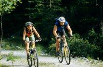 Uomo e donna in bicicletta su strada — Foto stock