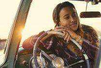 Mujer joven apoyada contra el volante en camioneta en Newport Beach, California, EE.UU. - foto de stock
