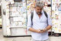Mature man reading smartphone texts on street, Copacabana town, Rio De Janeiro, Brazil — Stock Photo