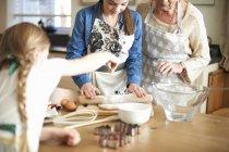 Pâte de roulement de femme et de petites-filles aînées pour des biscuits d'arbre de Noel — Photo de stock
