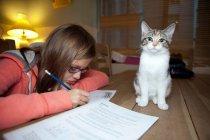 Девочка учится с котом на столе — стоковое фото