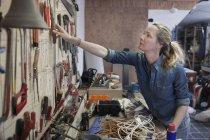 Mulher em oficina de alcançar ferramentas penduradas na parede — Fotografia de Stock