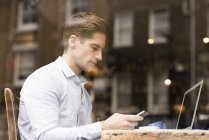 Window view of young businessman reading smartphone texts in cafe — Stock Photo