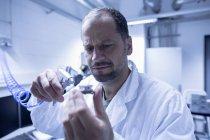 Assistante de laboratoire fixant une partie de l'équipement de laboratoire — Photo de stock
