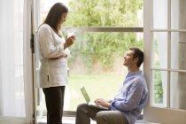 Mature couple talking at patio door — Stock Photo