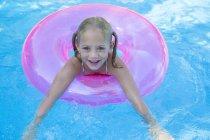 Portrait of girl in inflatable ring in garden swimming pool — Stock Photo