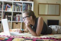 Teenage girl lying on front using laptop — Stock Photo