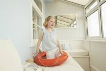 Girl playing with life belt on holiday apartment seat — Stock Photo