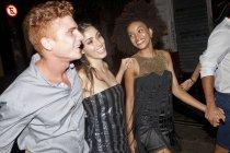 Quattro amici che camminano per strada insieme di notte — Foto stock