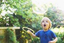 Мальчик делает огромный пузырь на заднем дворе — стоковое фото