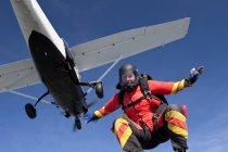 Женщина свободно прыгает с парашютом с самолета — стоковое фото