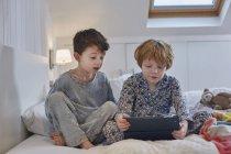Хлопчики в піжамі, використовуючи цифровий планшетний в ліжку — стокове фото
