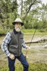 Bearded man by river holding fishing rod looking at camera — Stock Photo