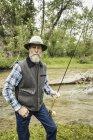 Homem barbudo por rio segurando haste de pesca olhando para a câmera — Fotografia de Stock