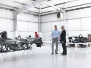 Salesman discussing supercar with customer in factory — Stock Photo