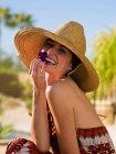 Giovane donna che indossa cappello da sole e che tiene petalo di fiore viola, ritratto — Foto stock