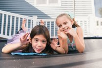 Girls lying on trampoline, looking at camera and making faces — Stock Photo