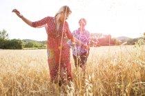 Jovem mulher com namorado dançando no campo de trigo, Maiorca, Espanha — Fotografia de Stock
