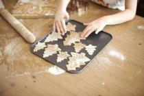 Mani della ragazza posa dell'albero di Natale cookies sul vassoio di cottura — Foto stock
