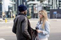 Couple multi ethnique parler et debout dans la rue — Photo de stock