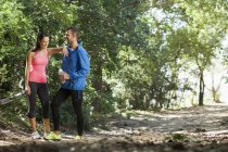 Young joggers taking break in forest — Stock Photo