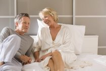 Couple reclining on bed chatting — Stock Photo