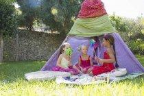 Tre ragazze che giocano con le ruote di perno davanti a teepee — Foto stock