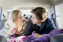 Jeune couple couché en véhicule récréatif, souriant — Photo de stock