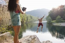 Woman photographing boyfriend jumping from rock ledge, Hamburg, Pennsylvania, USA — Stock Photo