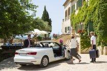 Boutique hotel porter con bagagli per coppie che arrivano in cabriolet, Maiorca, Spagna — Foto stock