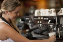 Young female waitress preparing coffee in cafe — Stock Photo