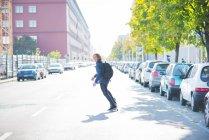 Dévier de jeune skateur urban male skateboard sur route — Photo de stock