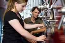 Cervejarias femininas e masculinas que trabalham em cervejaria — Fotografia de Stock