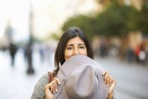 Woman holding hat over mouth on street — Stock Photo