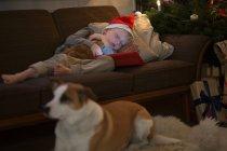 Мальчик в шляпе Санты спит на диване — стоковое фото