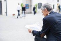 Homme d'affaires principal s'asseyant dans la place de ville affichant le journal de feuille large — Photo de stock