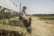 Man sitting on hay bale using laptop — Stock Photo