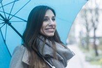 Портрет молодой женщины на улице, держащей синий зонтик — стоковое фото
