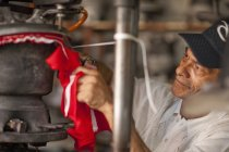 Hat maker cutting and stretching fabric in workshop — Stock Photo
