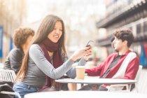 Жінка, сидячи на тротуарі кафе дивлячись на смартфон посміхаючись — стокове фото